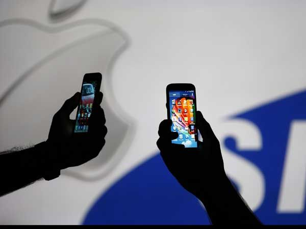 Men are silhouetted against a video screen with Apple and Samsung logos as he poses with Samsung S3 and Samsung S4 smartphones in this photo illustration taken in the central Bosnian town of Zenica