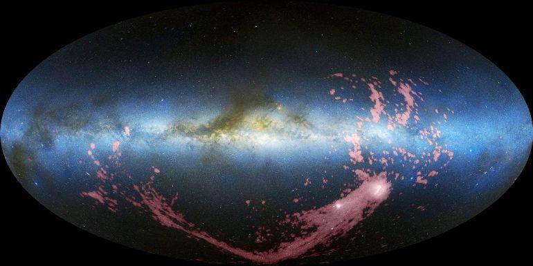 A Corrente Magalhânica (colorida artificialmente de rosa na imagem acima) origina-se nas Nuvens de Magalhães (manchas brancas na porção inferior direita) e se choca com a Via Láctea (faixa azulada horizontal). Crédito: Nidever, et al., NRAO/AUI/NSF e Mellinger, LAB Survey, Parkes Obs., Westerbork Obs., Arecibo Obs..