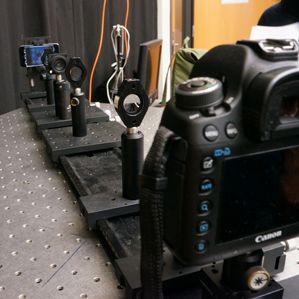 """Pesquisadores usam uma câmera e lentes para simular um olho com miopia olhando para um """"E"""" mostrado em uma tela iPod Touch modificado"""