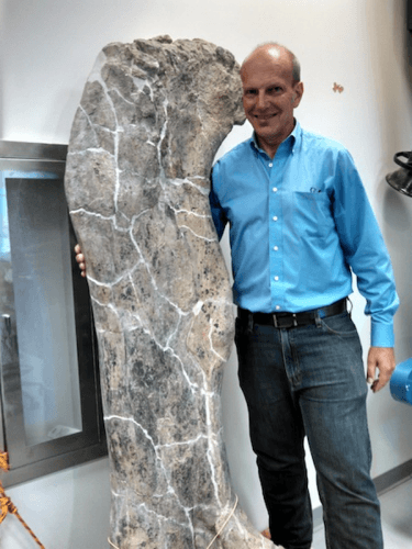 O paleontólogo Ken Lacovara posa ao lado do fêmur do Dreadnaughtus. Crédito: Francie Diep