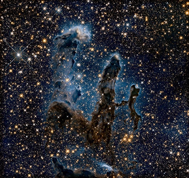 """Vistos em infravermelho, técnica que nos permite perceber o que há por trás da maior parte da poeira, os Pilares da Criação mostram contornos mais delicados, com destaque para a """"névoa"""" azul que contrasta com a poeira escura e a luz de inúmeras estrelas. Crédito: NASA/ ESA/Hubble/Hubble Heritage Team"""