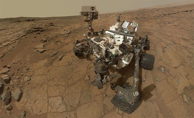 """""""Selfie"""" da sonda Curiosity na superfície de Marte. A imagem é, na realidade, uma composição de dezenas de imagens obtidas pelo jipe-robô em Fevereiro de 2013. No quadrante inferior esquerdo, é possível observar dois pequenos buracos escavados pela broca da Curiosity para recolher material amostral.  Crédito: NASA/JPL-CALTECH/MSSS"""