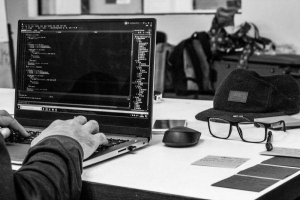 Homem em notebook alterando códigos