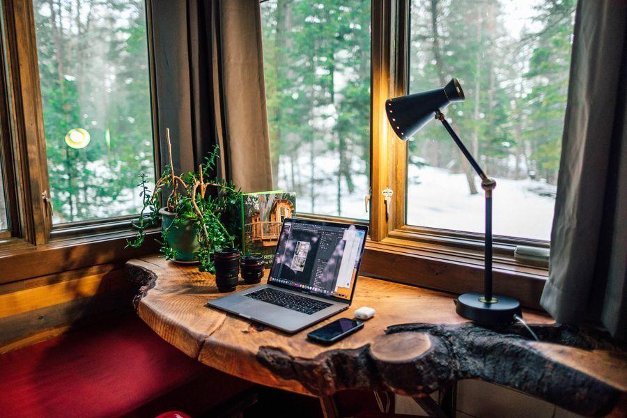 Mesa de trabalho com notebook e vista para paisagem